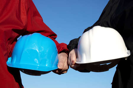two hard-hats (blue and white color) focus on hand of man