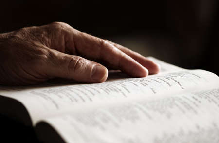 religious service: reading bible (special photo toned fx, focus point on hand (finger))