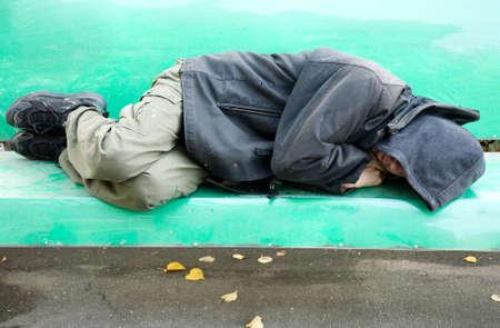 vagabundos: hombre durmiendo en el banco Foto de archivo