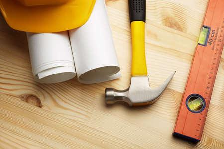 blueprints ,helmet,hammer  and level on wooden background photo
