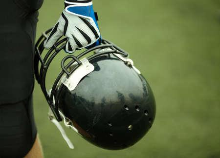 uniforme de futbol: mano del jugador con casco negro, enfoque selectivo  Foto de archivo