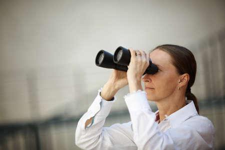 woman looking through binoculars ,business or lifestile concept photo