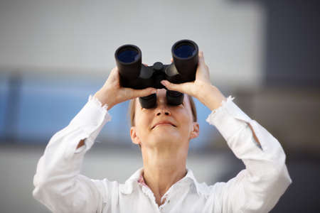 middle-aged woman with binocular, selective focus   photo
