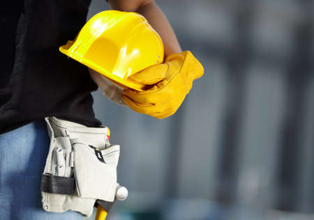 黄色いヘルメットと建物のサイト上の作業用手袋のビルダー