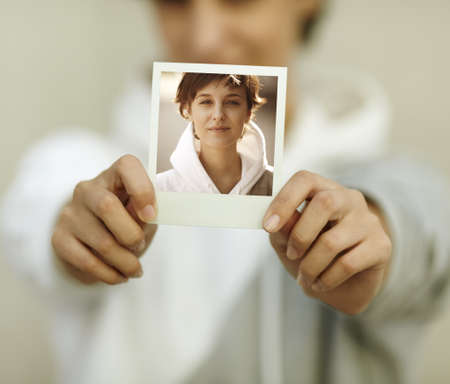 color photographs: young woman hold self-portrait, selective focus on foreground (photo made by me)
