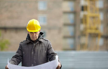 real builder with blueprints on construction site, natural light, focus on foreground photo