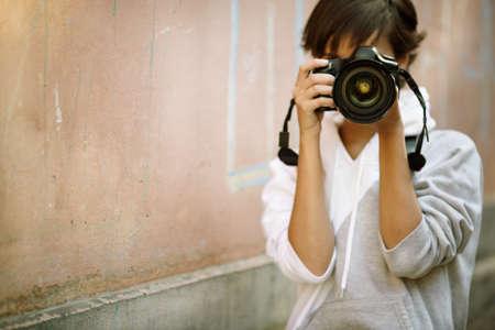 vrouwelijke foto graaf met professionele SLR camera, natuurlijke licht, selectieve focus op het dichtstbijzijnde deel van lens met mix Stockfoto