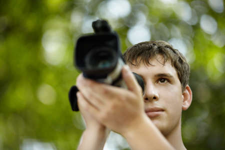 cinematograph: teen with camcorder capturing, selective focus on eye, natural light Stock Photo