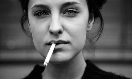 joven fumando: real joven mujer fuma  Foto de archivo