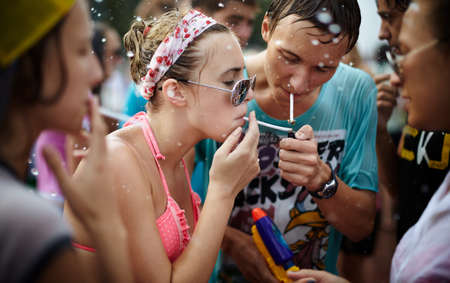 wet girls and young man taking a break and smoking a cigarettes. Photo taken in Samara city,Russia during a Water Wars flashmob Editorial