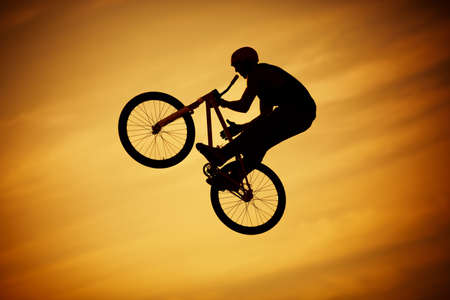 bmx bike: bmx jump on bright orange sky background Stock Photo