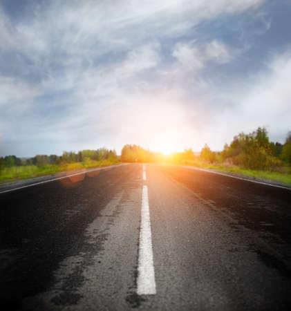 single lane road: Road Running Through Fields Stock Photo