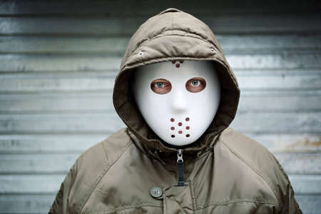 hoodlum: Spooky man with mask on the street Stock Photo