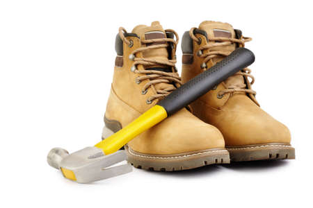 Working boots and hammer isolated on white background, selective focus photo