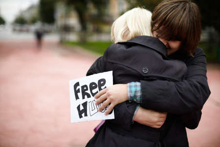 Samara,Russia - September 25, 2011: A young man hug blonde woman  on the street,  holding a paper offering free hugs to anyone on the gloomy and rainy autumn sunday Editorial