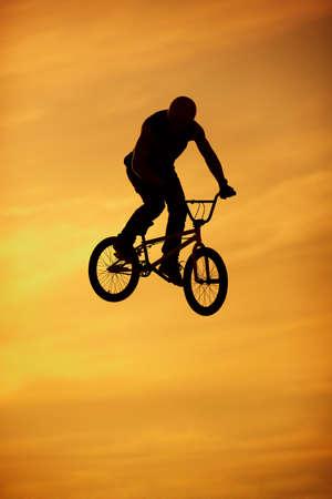 bmx jump on bright orange sky background photo