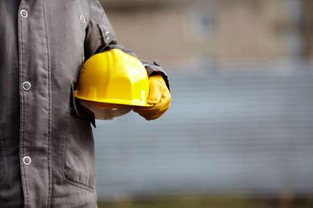 obreros trabajando: mano de constructor con casco amarillo Foto de archivo