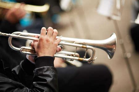 trompeta: banda de jazz tocando en la calle, el enfoque selectivo en las manos con la trompeta