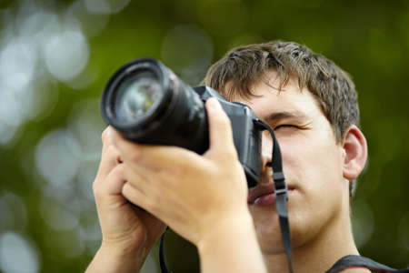 human photography: young man with black professional camera, natural light, selective focus on eye