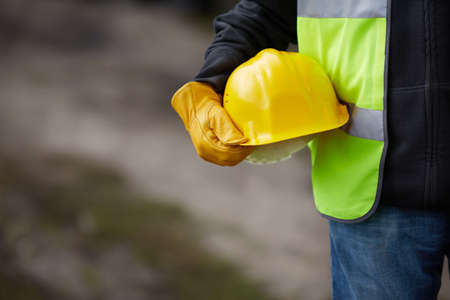 building site: builder with yellow helmet and working gloves on building site