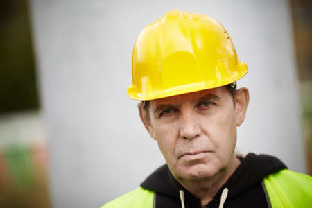 manual worker: Real experienced builder with yellow hardhat