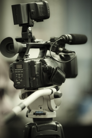 professional camcorder on the tripod, selective focus on nearest part Standard-Bild