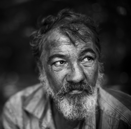 real homeless man on the dark background, selective focus on eye Stock Photo
