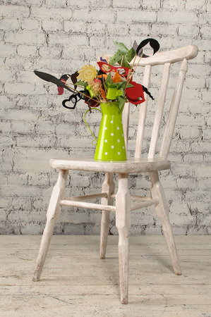 wall decor: Green pitcher with the decor inside is a wooden chair on the brick wall background