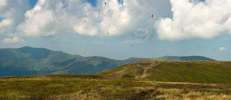 Competitions of paragliders on the ridge of Borzhava in the Carpathians in Ukraine. Panoramic photo of a large group of paragliders in the sky above the mountains.