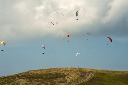 Competitions paragliders on the ridge Borzhava in the Carpathians in Ukraine. A large group of paragliders. Фото со стока - 83943352