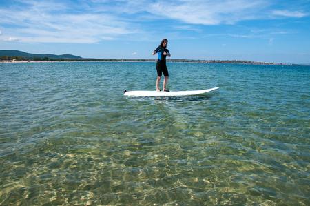 windsurf: Una mujer se para sobre una tabla de surf en el mar. Una niña aprende a montar en windsurf en la playa de Goldfish en Sozopol, Bulgaria.