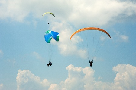Paragliding in the blue sunny sky. Three paraglider fly in summer sunny day. Carpathians, Ukraine. Stock Photo
