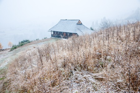 Snow-covered wooden house in beautiful autumn mountains. Dramatic scene with the end of fall and the beginning of winter in mountains.