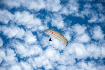 White paraglider flying in the blue sky against the background of clouds. Paragliding in the sky on a sunny day.