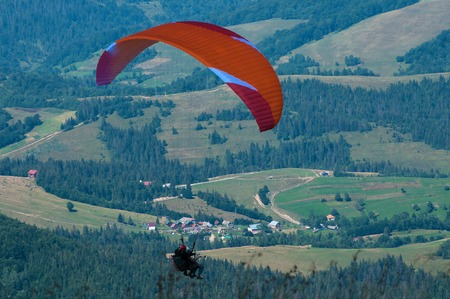 Tandem flies over a mountain valley on a sunny summer day. Paragliding in the Carpathians in the summer.