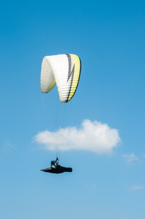 Alone paraglider flying in the blue sky against the background of clouds. Paragliding in the sky on a sunny day. Stock Photo