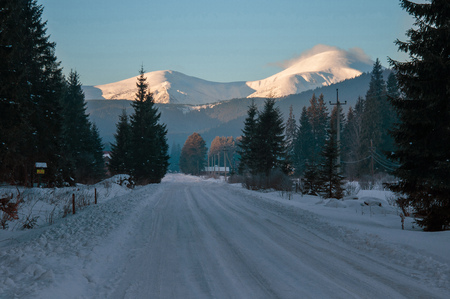 Winter road in the Carpathian mountains in the village. Snow-covered road that leads to the highest mountain peak in Ukraine - Hoverla.