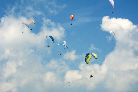 Paragliding in the blue sunny sky. Group of paragliders in the Carpathians. Paragliders against the background of clouds. Stock Photo