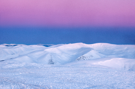 Wonderful sunrise in the Carpathians in the winter. Snow-covered summits of winter mountains in the red rays of sunrise. Fresh footprints in the snow on top of the mountain.