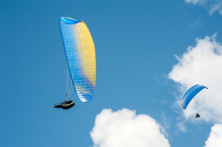 Two paragliders flying in the blue sky against the background of clouds. Paragliding in the sky on a sunny day. Stock Photo