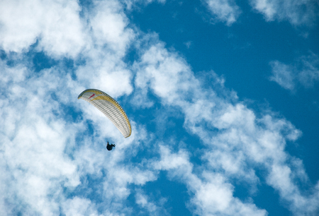 Paraglider flying in the blue sky against the background of clouds. Paragliding in the sky on a sunny day. Фото со стока