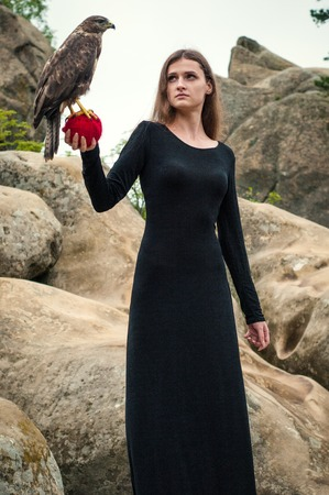 Beautiful girl holding a falcon in her arms. Brunette among the rocks holding a wild bird on a ball of red threads. Stock Photo