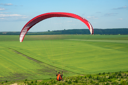 Paragliding over the green field in summer sunny day. One paraglider fly over a green field near Dnister river in Ukraine.