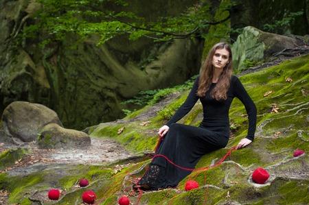 Allein schönes Mädchen sitzt auf grünem Moos in einem Märchenwald. Porträt einer Brünetten in einem schwarzen Kleid, das auf dem grünen Moos liegt, und um verstreute Kugeln eines roten Fadens.