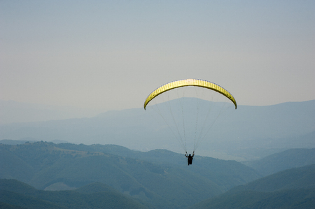 Paraglider flies over a mountain valley on a sunny summer day. Paragliding in the Carpathians in the summer. Imagens