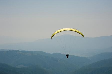 Parapente vuela sobre un valle de montaña en un día soleado de verano. Parapente en los Cárpatos en el verano. Foto de archivo
