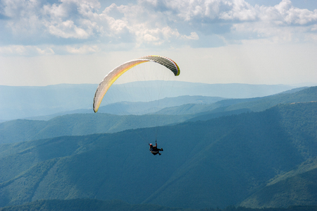 Paraglider takes off from the mountainside in the Carpathian Mountains. Paragliding in the mountains in the summer.