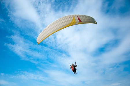 One paraglider flying against the background of clouds. Paragliding in the sky on a sunny day. Фото со стока