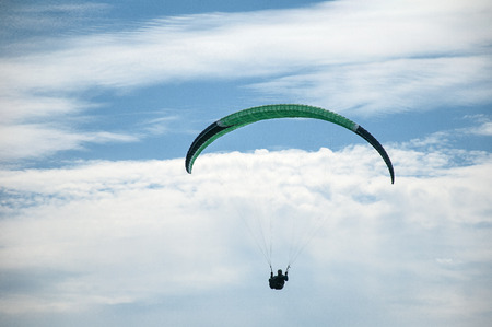 One paraglider flying against the background of clouds. Paragliding in the sky on a sunny day. 版權商用圖片