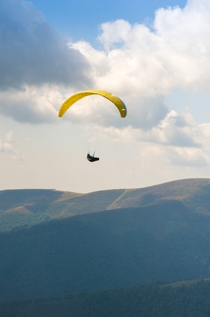 Paraglider fly over a mountain valley on a sunny summer day. Paragliding in the Carpathians in the summer.